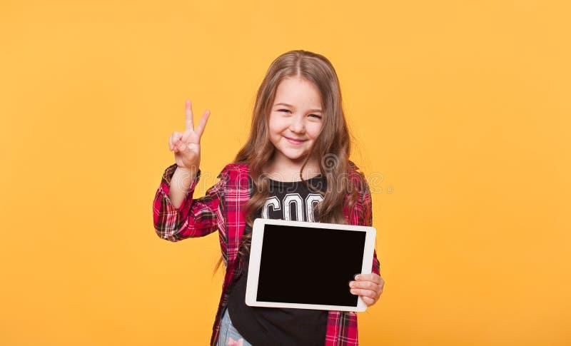 Criança feliz com computador da tabuleta Exibição da criança fotografia de stock royalty free