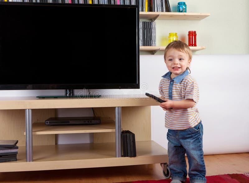Criança feliz com controlo a distância na frente da tevê foto de stock royalty free