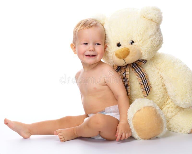 Criança feliz com o brinquedo macio grande do urso fotografia de stock