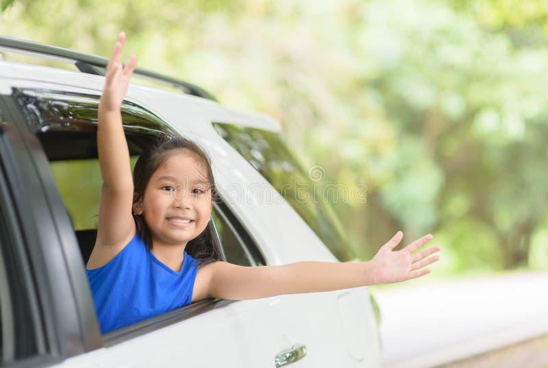 Criança feliz com os braços aumentados do carro da janela imagem de stock