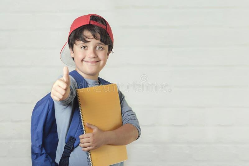 Criança feliz com trouxa e com caderno, de volta à escola fotos de stock royalty free