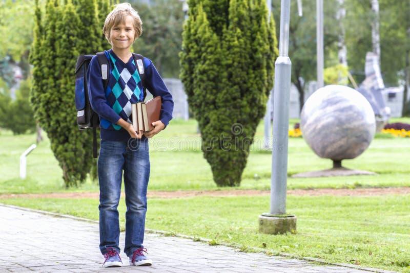 A criança feliz com uma trouxa e os livros vão à escola outdoor imagem de stock royalty free