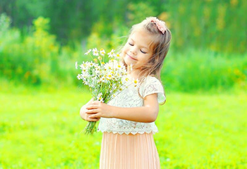 A criança feliz da menina do retrato com ramalhete floresce na mola foto de stock royalty free