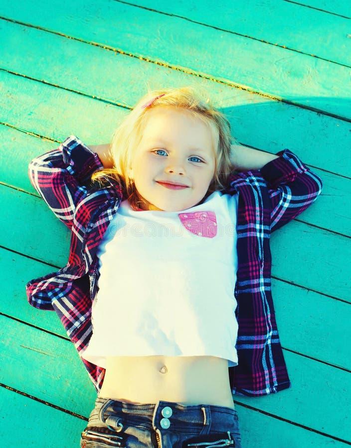 Download Criança Feliz Da Menina Que Descansa Em Um Assoalho De Madeira Imagem de Stock - Imagem de mãos, infância: 65576053