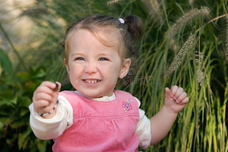 Criança feliz da menina que mostra excitedly fora um seixo. fotografia de stock royalty free