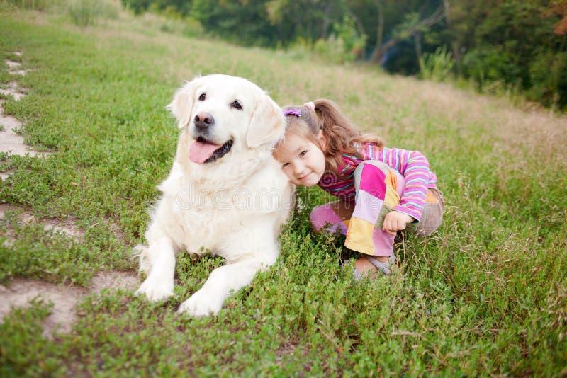 A criança feliz e um cão produzem dourado recuperam fotografia de stock royalty free