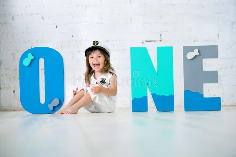Criança feliz em um terno do ` s do capitão com as letras uma em um fundo branco de uma parede de tijolo imagens de stock