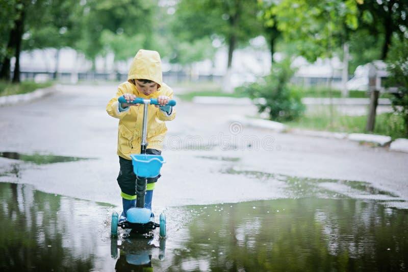 A criança feliz em uma capa de chuva amarela monta um 'trotinette' através da poça imagem de stock royalty free
