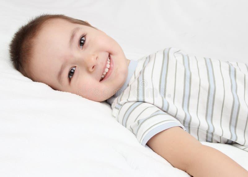 A criança feliz encontra-se na cama branca foto de stock