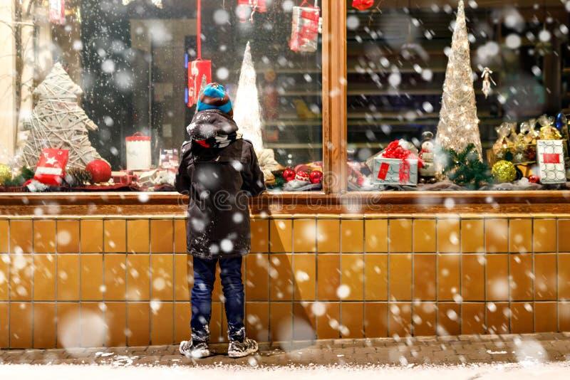 A criança feliz engraçada no inverno da forma veste a fatura da compra da janela decorada com presentes, árvore do xmas foto de stock royalty free