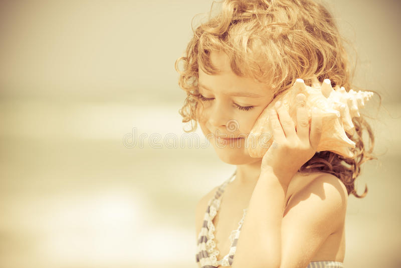 A criança feliz escuta a concha do mar na praia fotos de stock