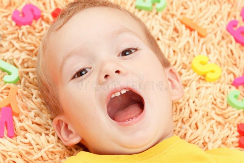 Criança feliz na roupa colorida que joga com letras plásticas Aprendendo o alfabeto, preparando-se para a escola fotografia de stock royalty free