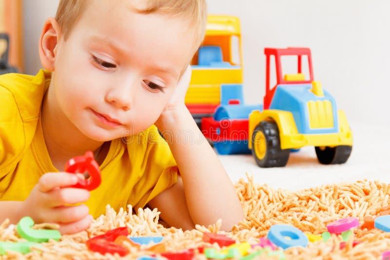 Criança feliz na roupa colorida que joga com letras plásticas Aprendendo o alfabeto, preparando-se para a escola fotografia de stock