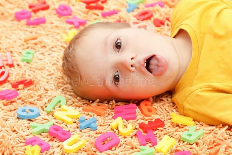 Criança feliz na roupa colorida que joga com letras plásticas Aprendendo o alfabeto, preparando-se para a escola imagens de stock royalty free