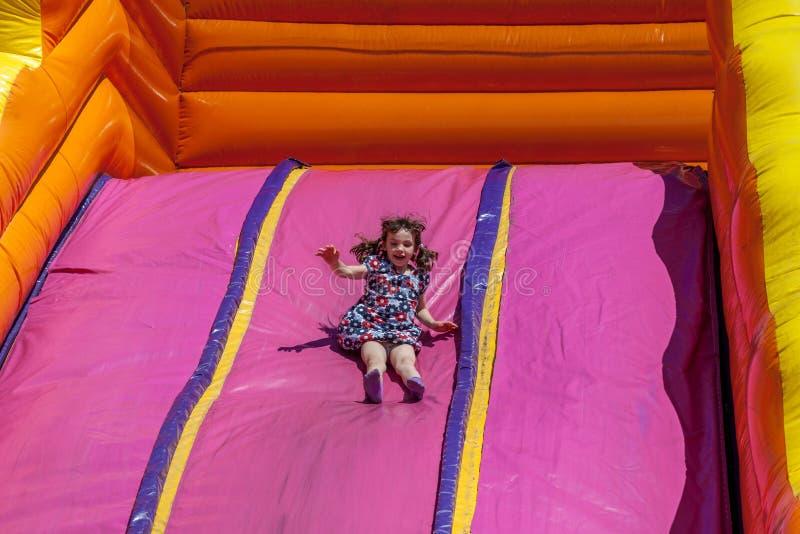 Criança feliz nova da menina no vestido que monta a corrediça inflável fora um dia de verão morno imagens de stock royalty free