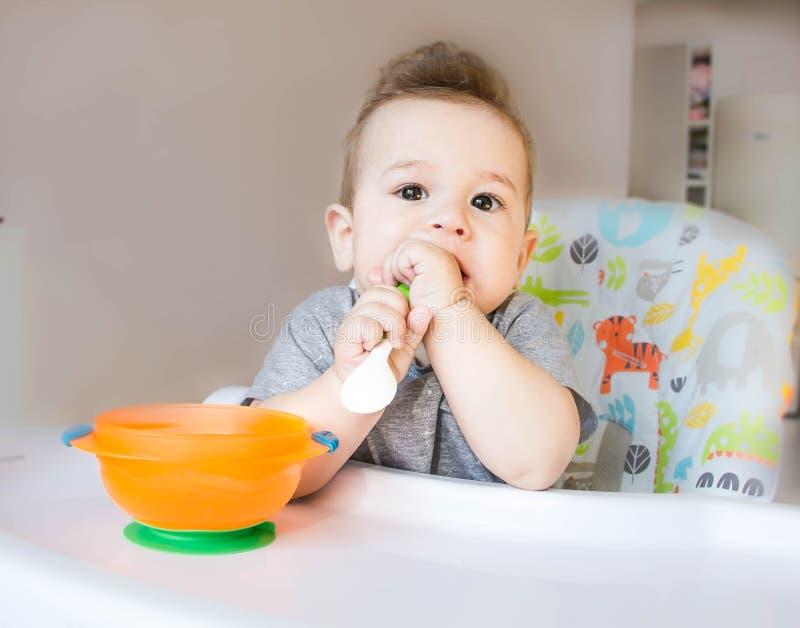 A criança feliz pequena que senta-se em uma cadeira e come do de quem cara seja estragada no comida para bebê, o conceito da famí fotos de stock