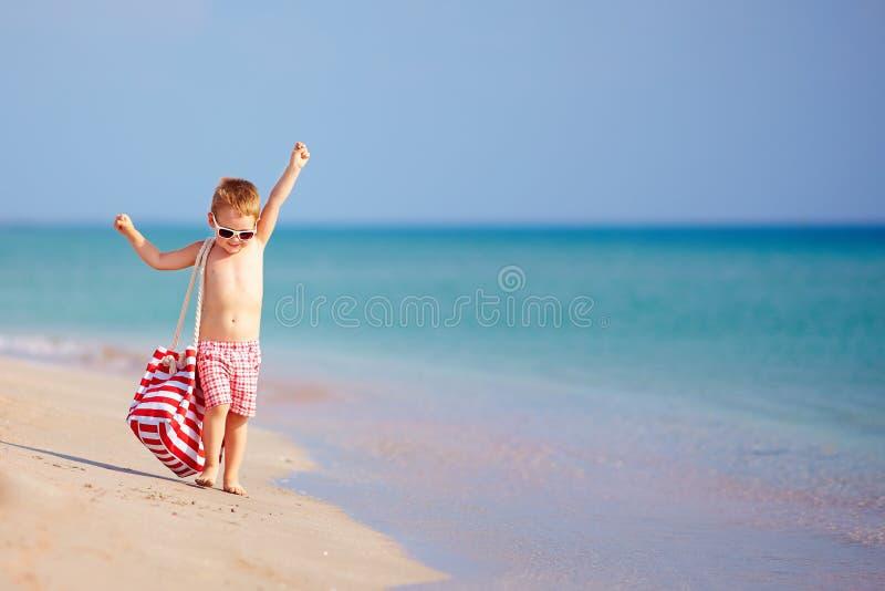 Criança feliz que anda a praia do verão imagem de stock