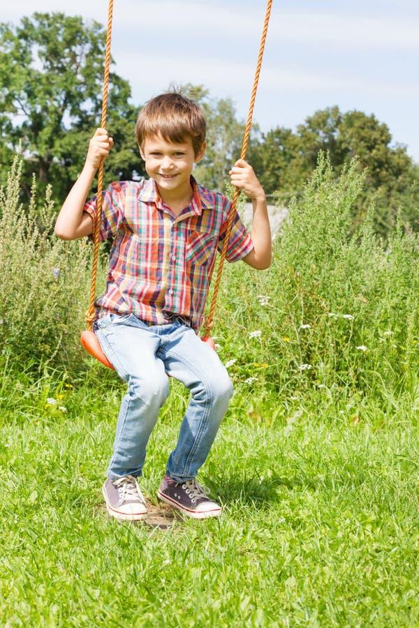 Criança feliz que balança no balanço exterior fotografia de stock
