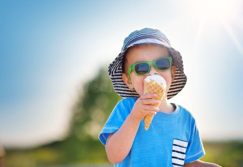 Criança feliz que come o gelado fora no verão imagens de stock royalty free