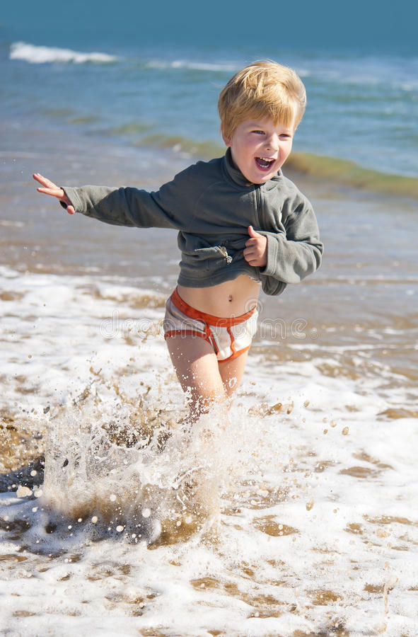 Criança feliz que corre na praia da costa de mar imagens de stock royalty free