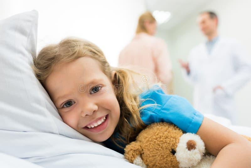 criança feliz que encontra-se na cama de hospital quando fala da mãe imagens de stock