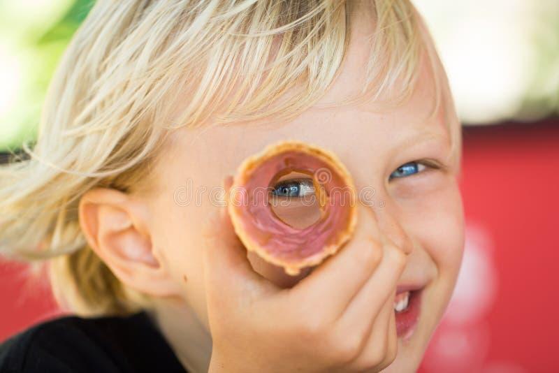 Criança feliz que espreita através do cone de gelado imagens de stock