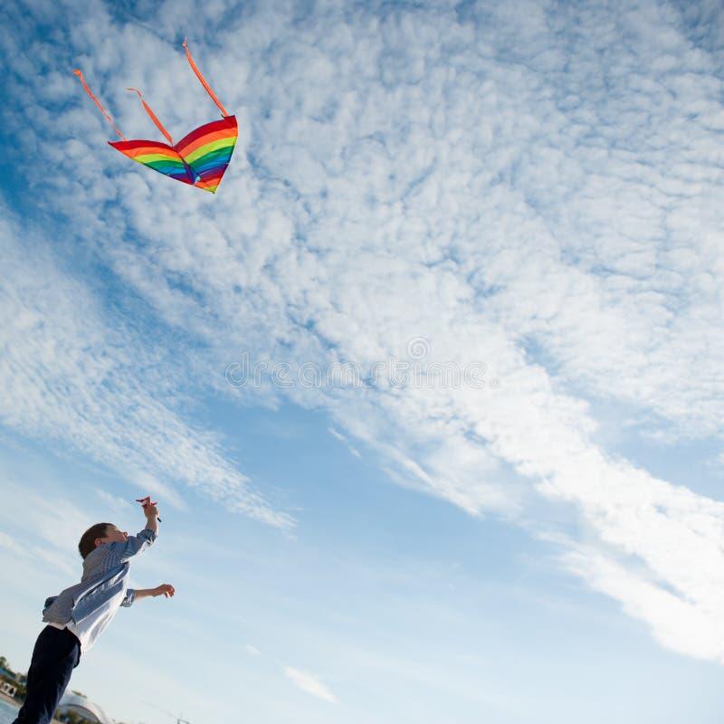 Criança feliz que guarda um voo do papagaio no céu bonito imagem de stock