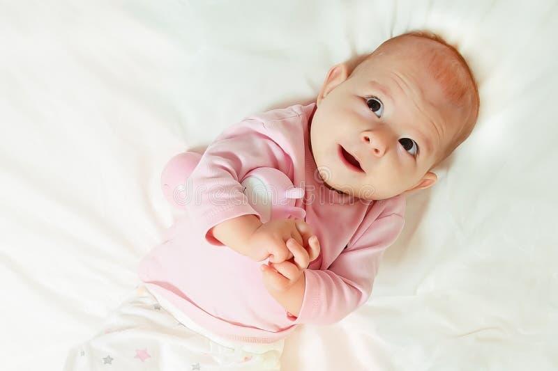 Criança feliz que imagina algo e o sorriso Encontro na cama foto de stock