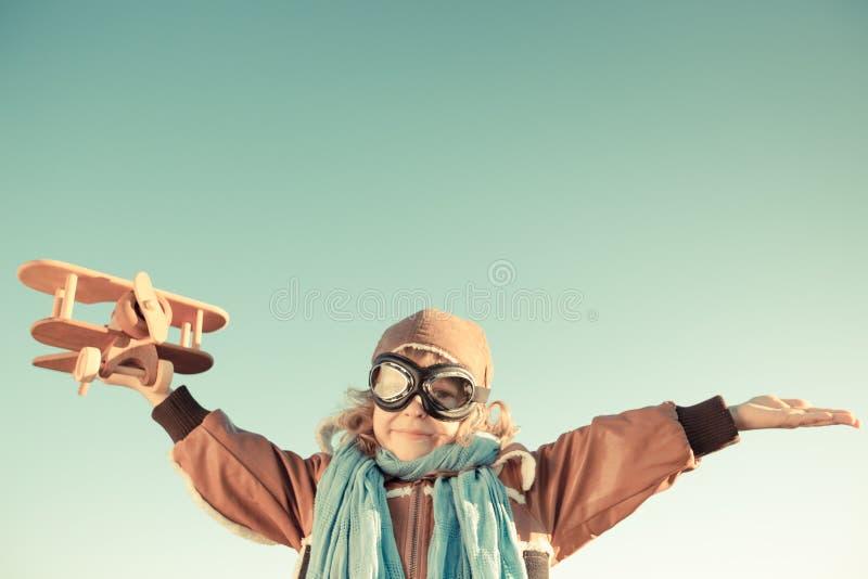 Criança feliz que joga com avião do brinquedo fotografia de stock