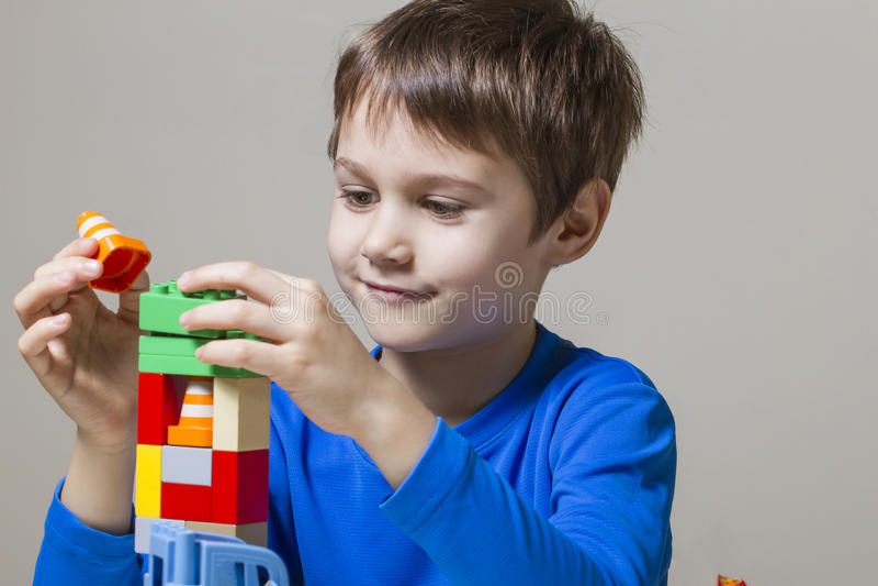 Criança feliz que joga com blocos plásticos coloridos do brinquedo da construção na tabela imagem de stock