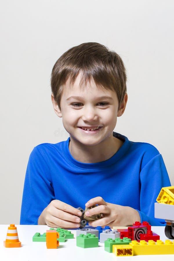 Criança feliz que joga com blocos plásticos coloridos do brinquedo da construção na tabela imagens de stock royalty free