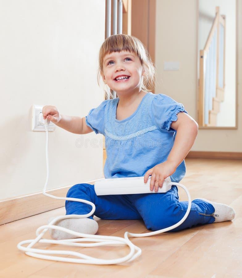 Criança feliz que joga com eletricidade em casa fotografia de stock royalty free