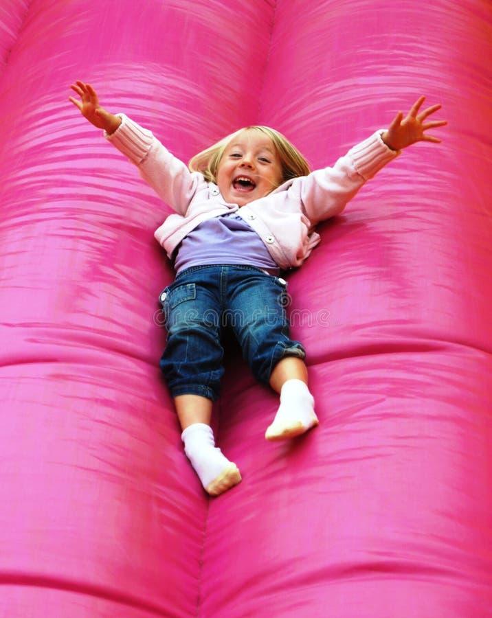 Criança feliz que joga na corrediça foto de stock
