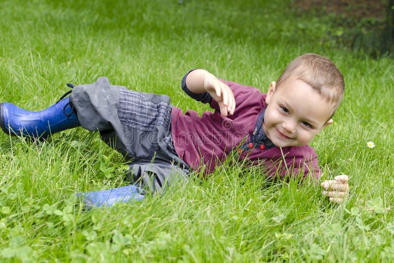 Criança feliz que joga na grama foto de stock