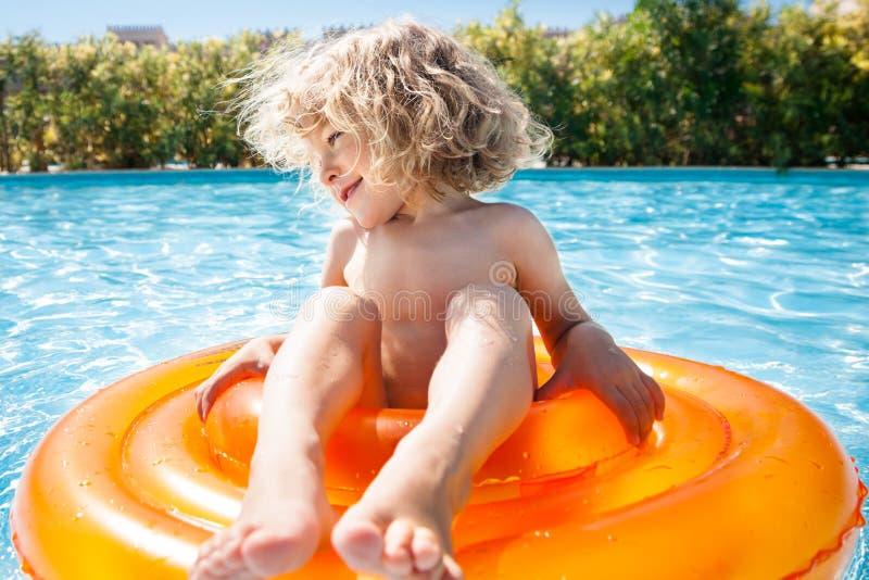 Criança feliz que joga na piscina foto de stock