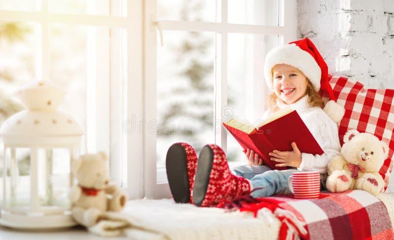 Criança feliz que lê um livro ao sentar-se em uma janela do inverno imagem de stock royalty free