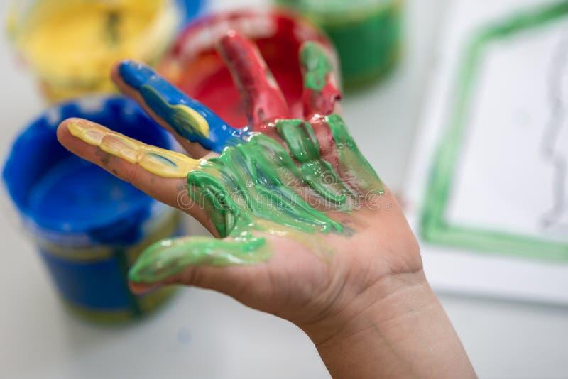 Criança feliz que mostra fora uma mão colorida foto de stock royalty free