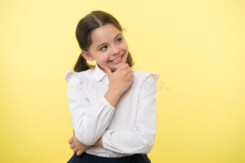 Criança feliz que pensa no fundo amarelo Menina pequena do daydreamer com sorriso bonito Perdido nos pensamentos Seus sonhos pode fotos de stock royalty free