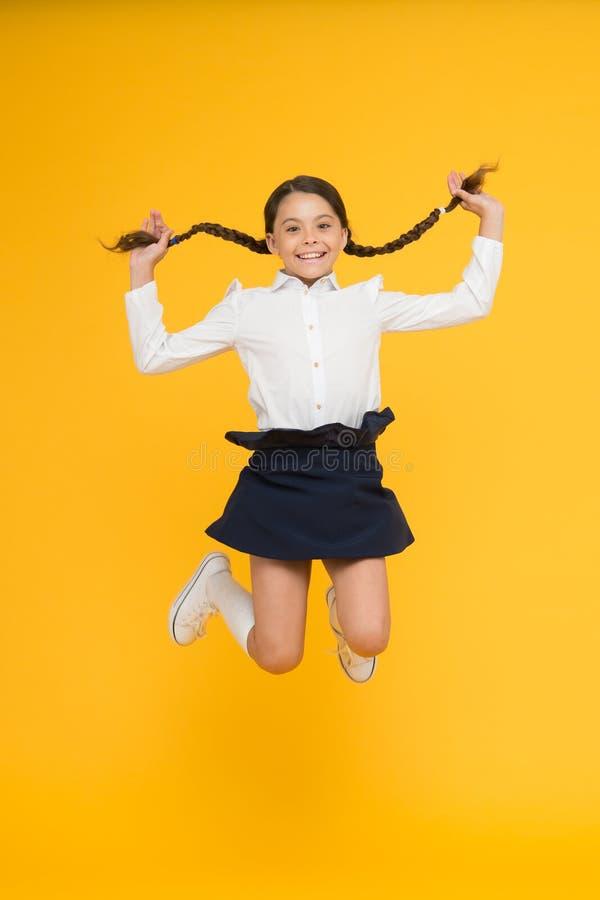 Criança feliz que salta na farda da escola Tendo o divertimento Hora para o divertimento Ruptura da escola salto e sentimento liv foto de stock