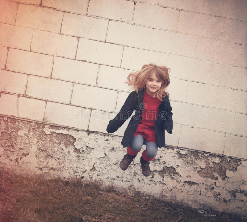 Criança feliz que salta no ar com a parede de tijolo velha imagens de stock royalty free