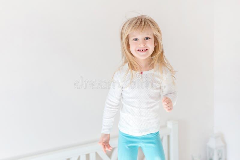 Criança feliz que salta sobre a cama Menina loura pequena bonito que tem o divertimento dentro Conceito feliz e descuidado da inf imagem de stock