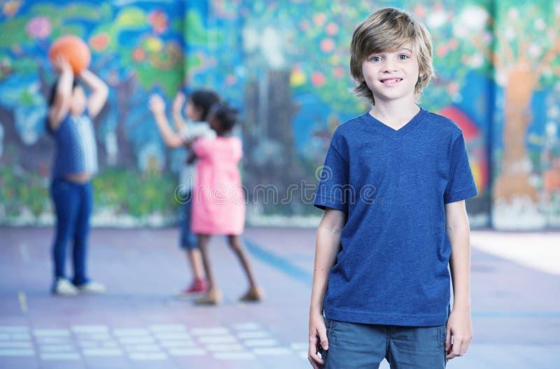 A criança feliz que sorri no recreio com outro chilldren o jogo sobre fotos de stock royalty free