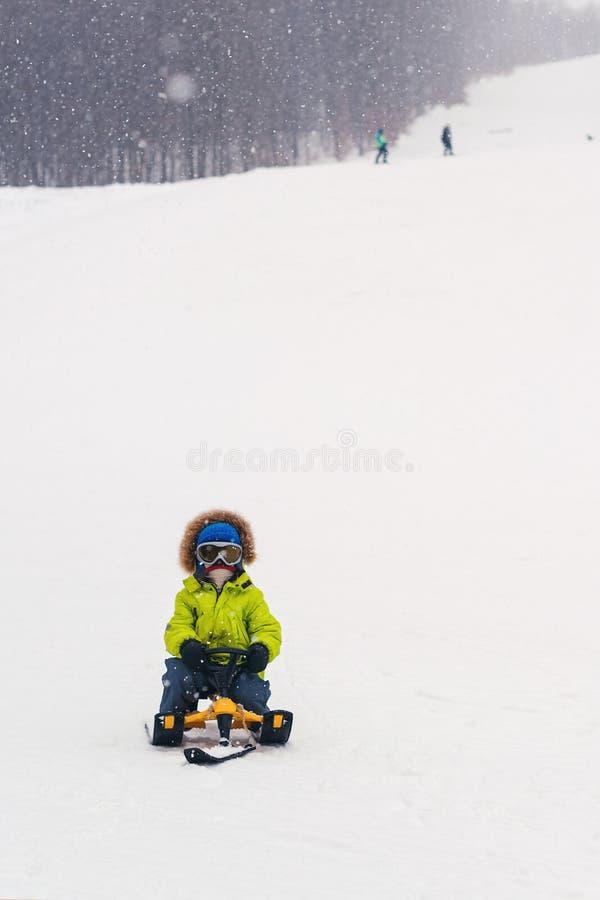 A criança feliz sledding no dia de inverno nevado Criança da criança que monta um pequeno trenó Feriados de inverno Infância feli fotos de stock