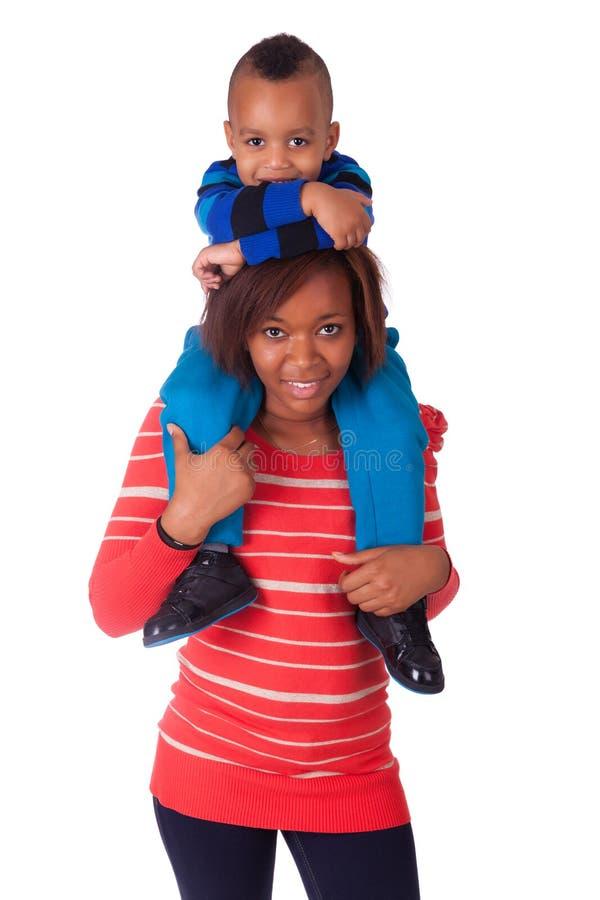 A criança feliz sorriu nos ombros de sua matriz fotos de stock royalty free