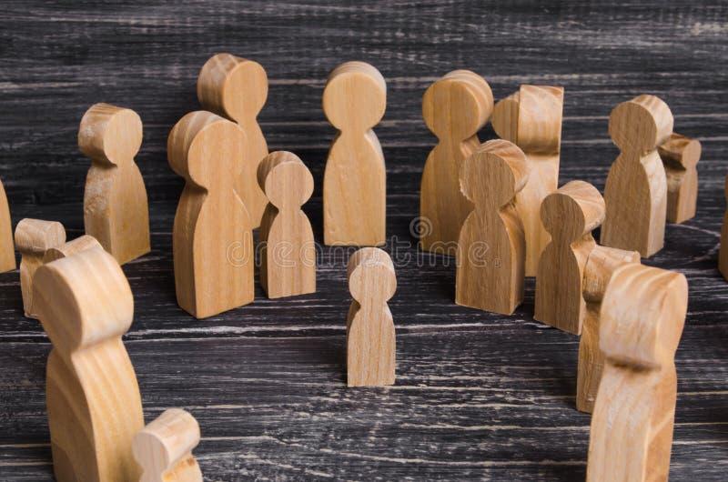 A criança foi perdida na multidão Uma multidão de figuras de madeira dos povos cerca uma criança perdida Miúdo perdido imagens de stock