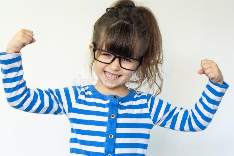 A criança forte engraçada inteligente mostra-nos seu bíceps Conceito do poder da menina fotografia de stock