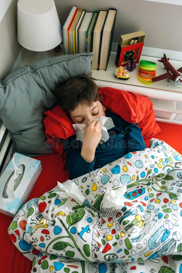 Criança fria que encontra-se na cama imagem de stock royalty free