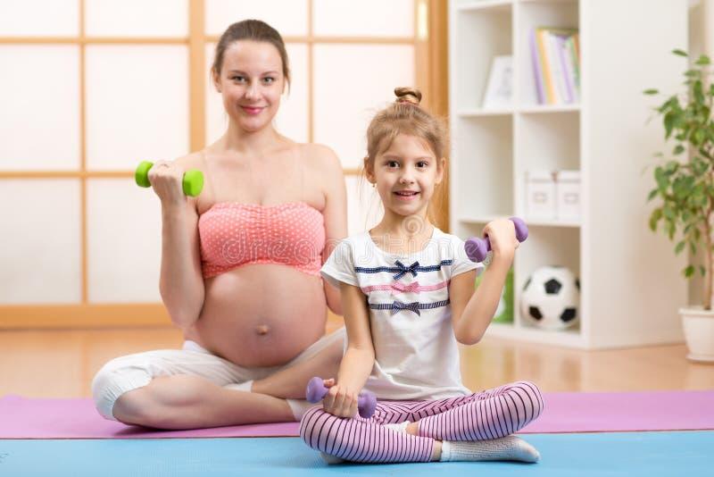 A criança grávida da mamã e da pessoa idosa contrata na aptidão imagens de stock royalty free