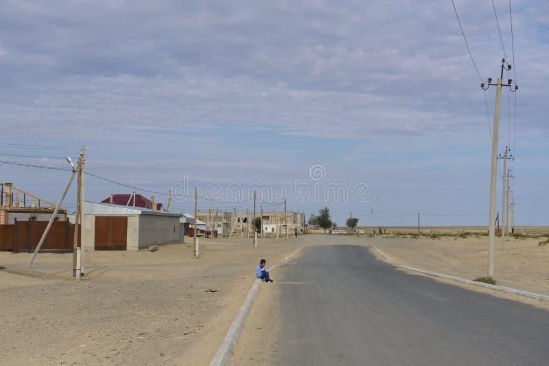 A criança grita no lado da estrada em Aralsk, Cazaquistão foto de stock