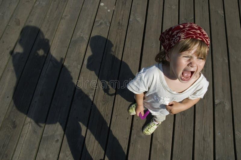 Criança gritando. menina doce com uma têmpera fotografia de stock royalty free